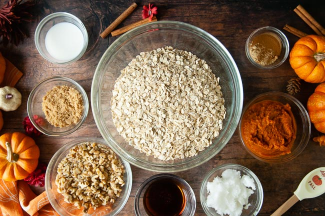 Glass bowls with the ingredients for pumpkin granola (milk, walnuts, pumpkin, coconut oil, pumpkin puree, spices and rolled oats) sit on a wooden table