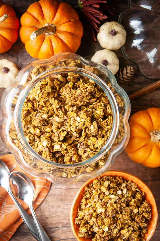 A glass pumpkin jar stores this homemade pumpkin granola so you can feel festive while you spoon it out into your orange cereal bowl.