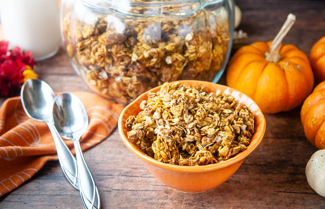A bowl of pumpkin granola in front of a glass jar of it makes a cozy fall breakfast scene.