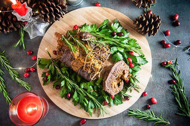 The perfect platter of beef roulade for the holidays on a wooden server surrounded by green