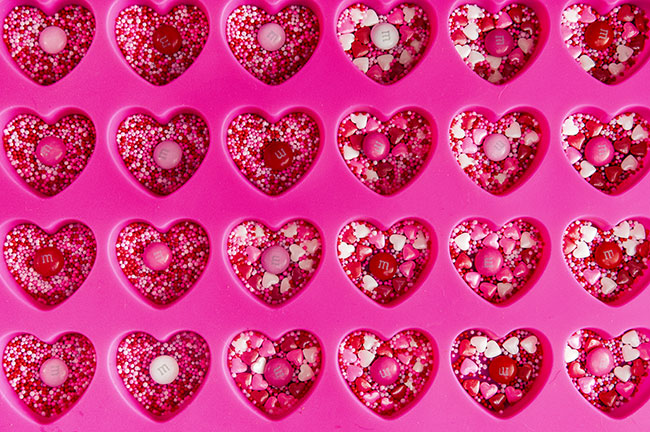 Pink, red, and white sprinkles in silicone heart molds
