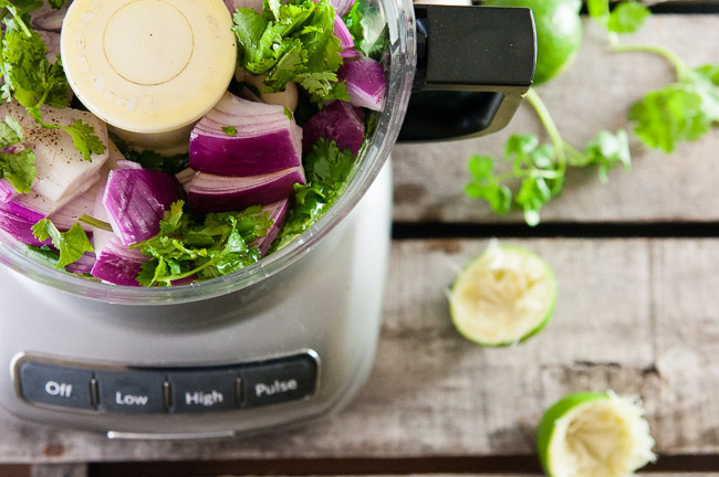 Herbs, red onion, garlic and lime in a food processor