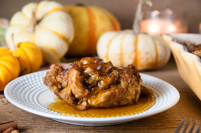 A slice of pumpkin French Toast Casserole on a white plate with syrup and pumpkins in the background