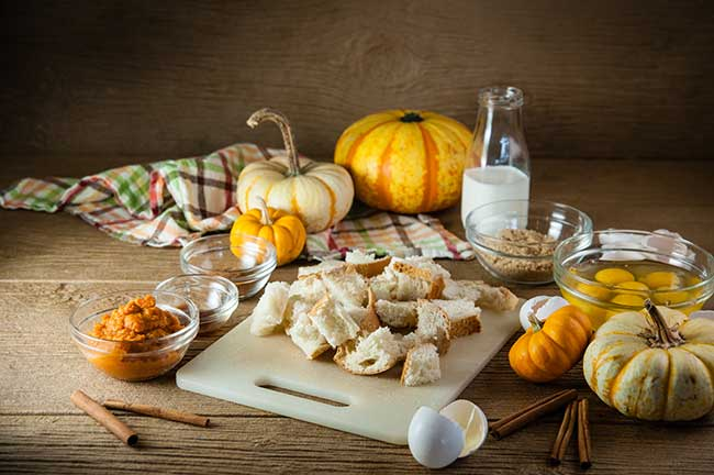 Ingredients for Pumpkin French Toast Casserole including bread cubes, cracked eggs, pumpkin puree, and spices laid out on a wooden table