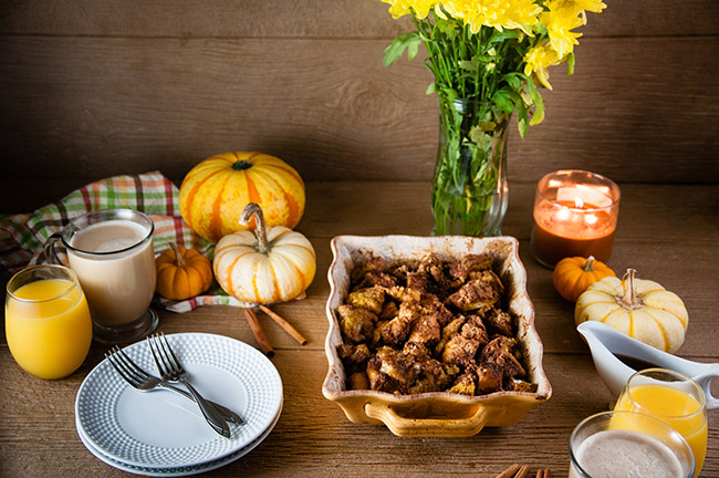 Pumpkin French Toast Casserole in a yellow baking dish with pumpkins and mums on the breakfast table