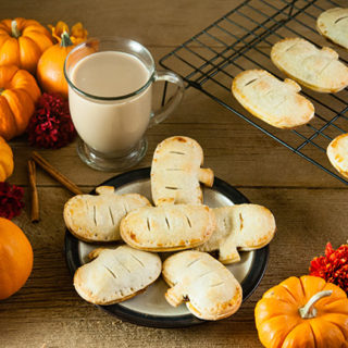Pumpkin hand pies on a plate on a wood table with coffee, pumpkins, flowers, a candle, and cinnamon sticks