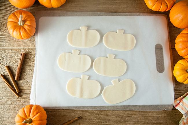 Pie crust in pumpkin shapes on a cutting board, surrounded by pumpkins and cinnamon sticks.