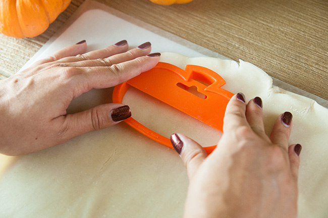 Woman's hands pressing an orange pumpkin cookie cutter into unrolled pie dough on a wood table