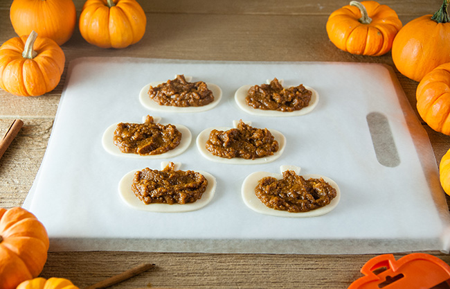 Pumpkin filling on pie crusts on a cutting board on a wood counter surrounded by small pumpkins