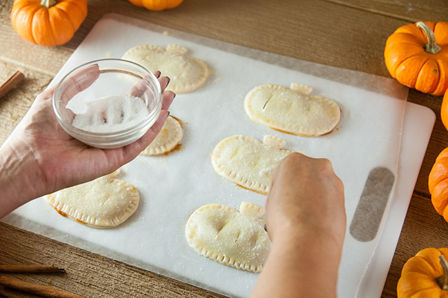 A woman's hands sprinkling sugar on pumpkin shaped pies.