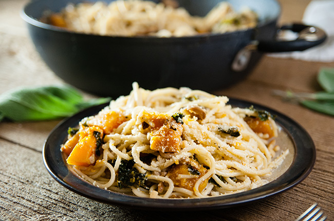 Spaghetti, kale, mushrooms, squash, garlic, sage, and walnuts on wood