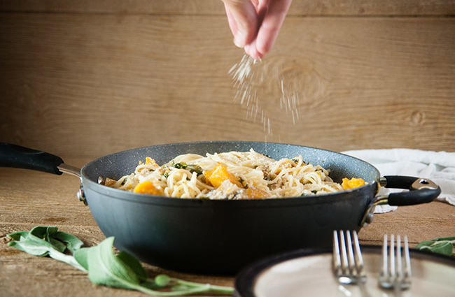 A hand sprinkling Parmesan cheese over a saute pan full of winter vegetable pasta