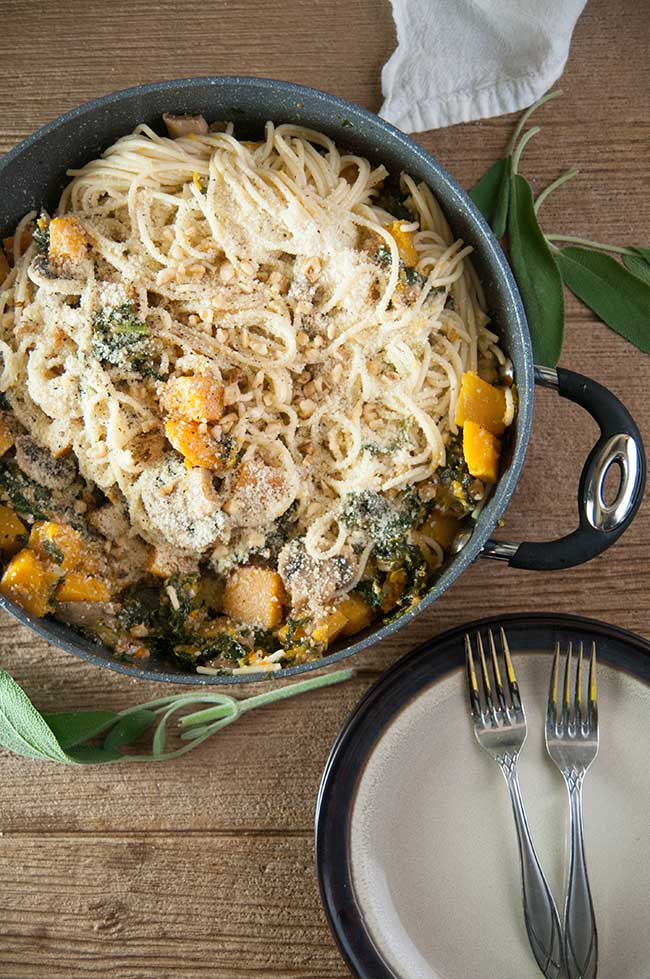 Winter Vegetable Pasta with Sauteed Butternut Squash, Kale, Mushrooms and Walnuts in a big pan with a plate and forks on wood