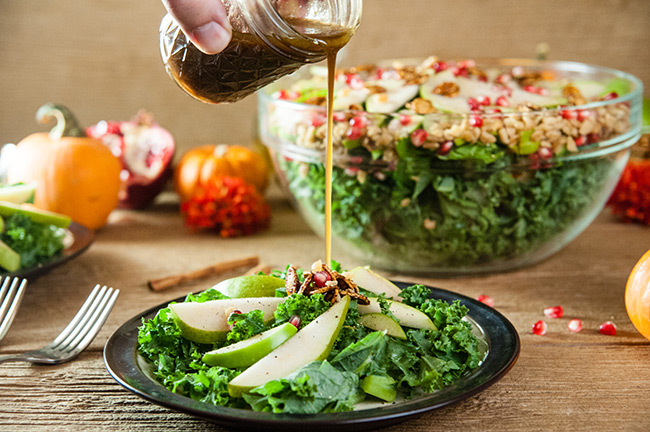 dressing being poured onto a plate of apple and pear kale salad sitting on a wood table with a large salad bowl and fall fruits behind it