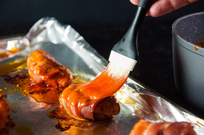 Homemade hot sauce being brushed onto wings