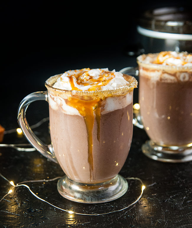 Slow Cooker Salted Caramel Hot Chocolate on a black surface and background