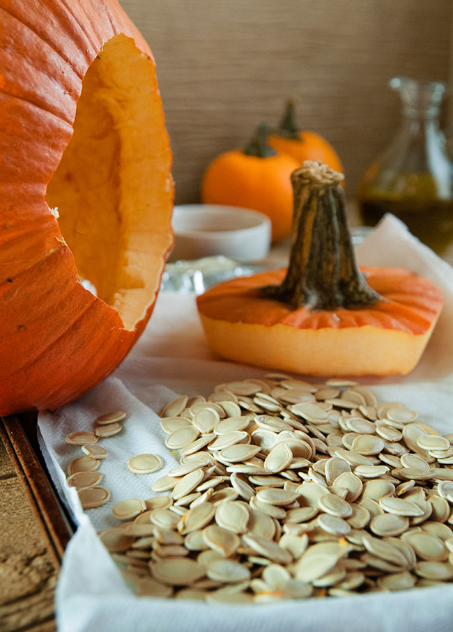 a hollowed out pumpkin on its side with the top cut off and a tray of pumpkin seeds