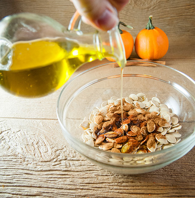 Pouring olive oil into a bowl of pumpkin seeds and spices