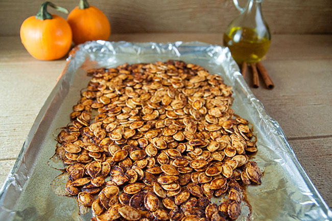 Spiced pumpkin seeds on a cookie sheet lined with aluminum foil