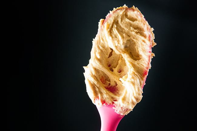 Cookie dough on a pink spoon against a black background