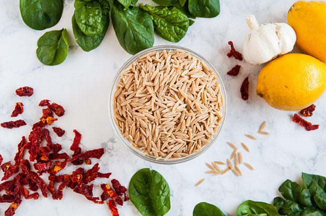 A bowl of orzo on a light background surrounded by lemons, garlic, spinach and sun dried tomatoes
