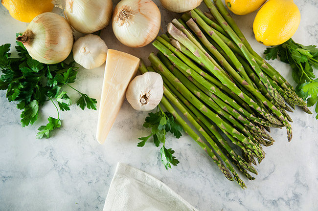 Onions, asparagus, parsley, and lemon on a white marble background
