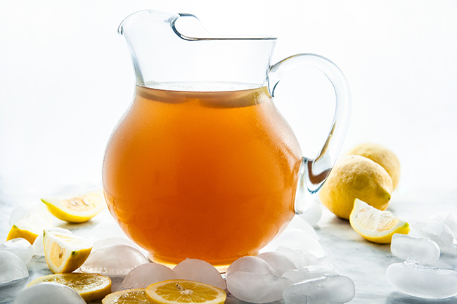 Homemade Iced Tea in a glass and glass pitcher with lemons and ice cubes on white