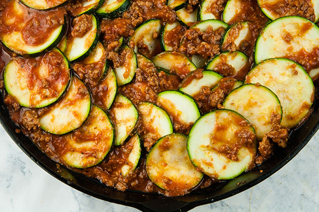 Zucchini slices in sauce in a skillet