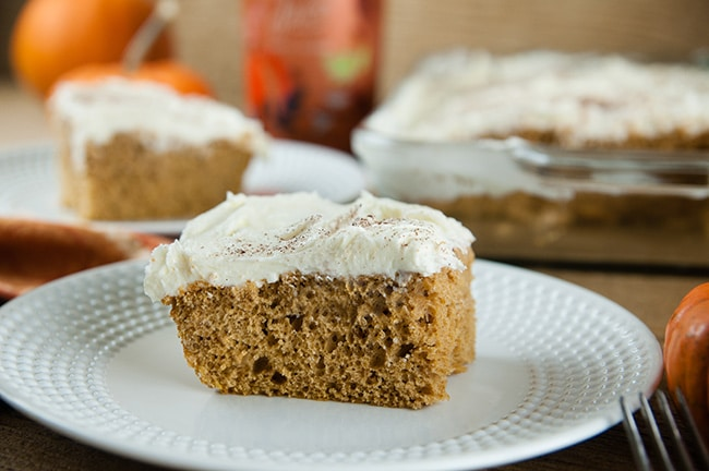 Square Slice of Boozy Pumpkin Sheet Cake on white plates on wood background