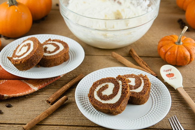 Boozy Pumpkin Spice Buttercream inside pumpkin rolls on wood