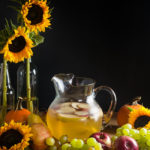 A pitcher of sangria with apples and pears on a wood table surrounded by harvest fruits, sunflowers, and twinkle lights