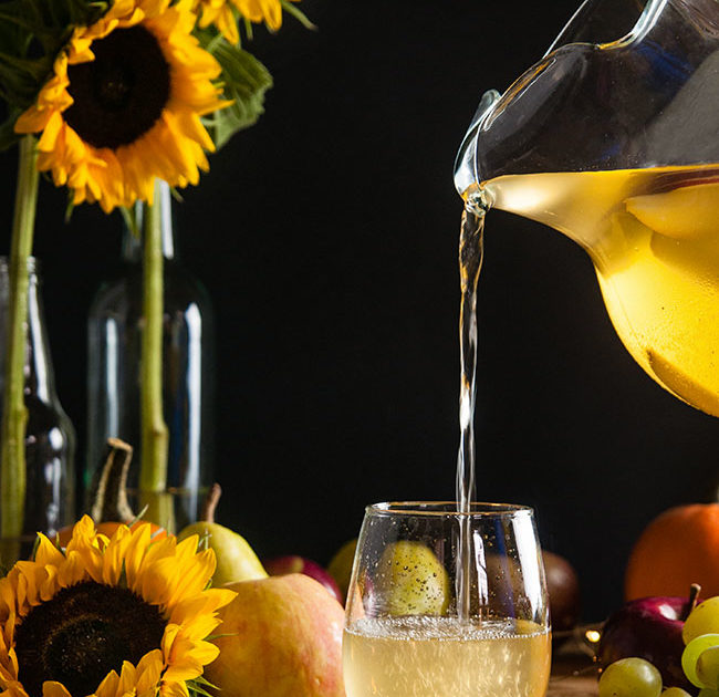White apple sangria in a pitcher being poured into a stemless wineglass on wood table with sunflower and harvest fruits