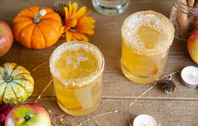Sparkling Caramel Apple Screwdrivers on wood with pumpkins, apples, and candles