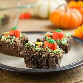 Plate with 3 pumpkin patch brownies on wood