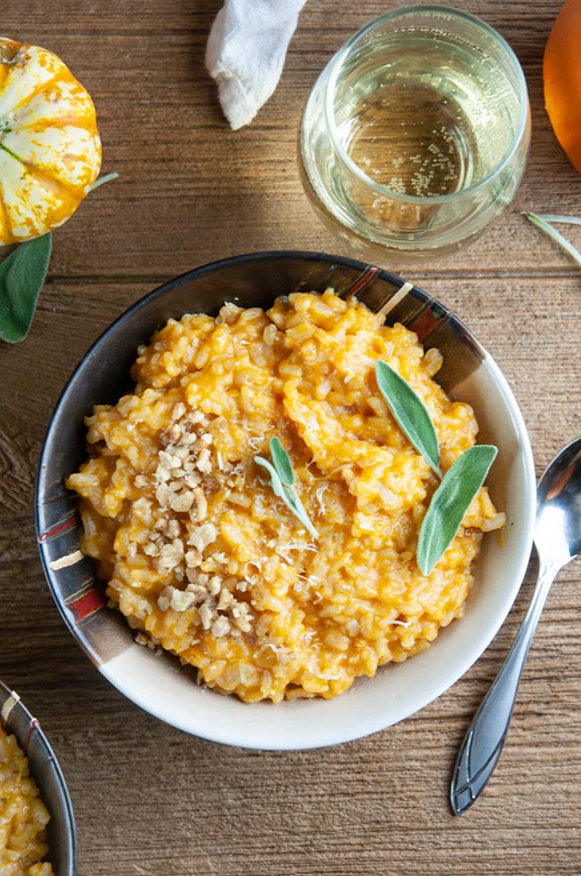 A bowl of pumpkin risotto on wood with wine and pumpkins