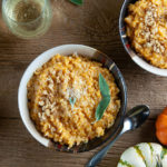 2 bowls of pumpkin risotto on wood with small pumpkins, glasses of white wine, and parmesan cheese