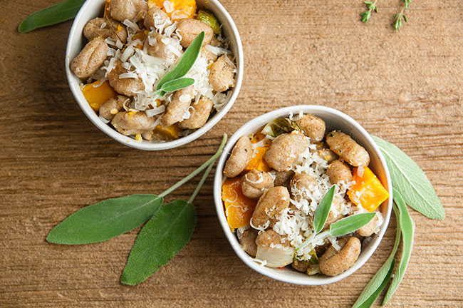 Roasted Sheet Pan Gnocchi in bowls on wood with sage and Fall Vegetables