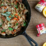 A skillet of Classic Homemade Stuffing on a wood background with orange slices, spice jars, and sage leaves