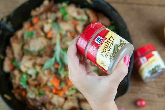 A child's hand holding McCormick® Poultry Seasoning over a pan of homemade stuffing