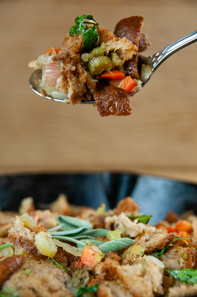 A spoonful of Classic Homemade Stuffing above a pan of stuffing on wood background