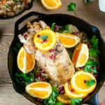 Garlic roasted turkey breast in a cast iron skillet with orange slices and greens on wood surrounded by dishes of mashed potatoes, stuffing, and gravy