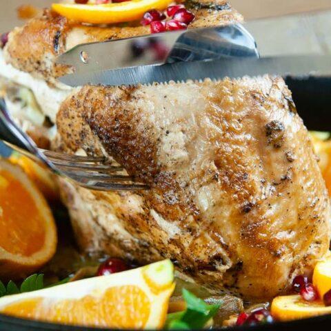 A knife cutting into a roast turkey breast on wood background