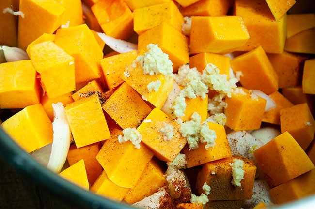 Cubed squash, rough chopped onions, garlic, and seasoning in the inner liner of the Instant Pot
