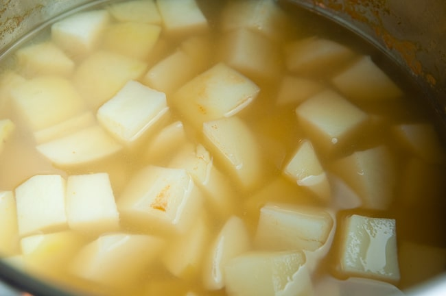 Cooked potato cubes in vegetable stock in an Instant Pot liner