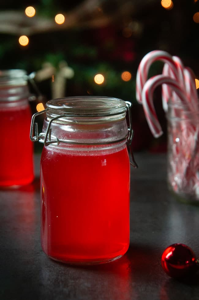 2 jars of red candy cane vodka on dark in front of Christmas trees and candy canes