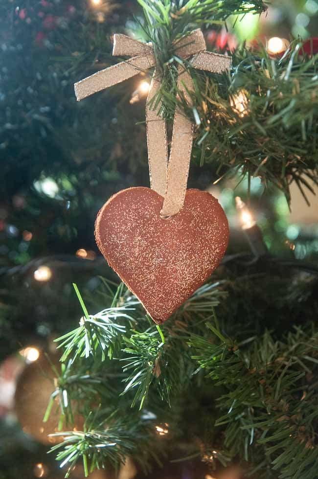 A cinnamon ornament shaped like a heart hanging on a Christmas tree