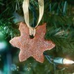 Easy cinnamon ornament shaped like a snowflake hanging on a Christmas tree