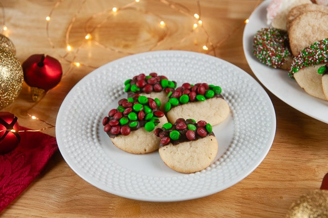 A plate of sugar cookies dipped in chocolate and M&Ms on wood with holiday ornaments and lights store bought sugar cookie dough hacks