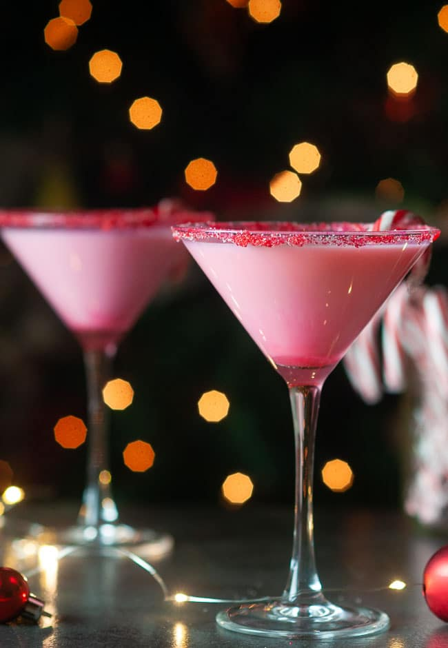 white chocolate candy cane martinis on a dark background in front of a christmas tree