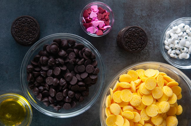 Ingredients for bumblebee cookies: yellow candy melts, chocolate chip, candy eyes, oil, Oreos, heart sprinkles